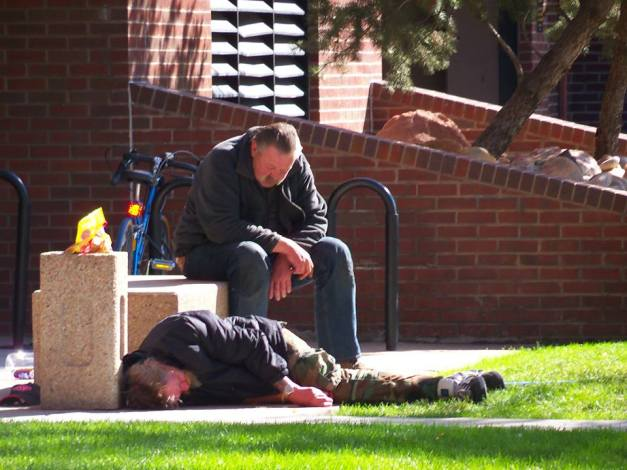 Two homeless men asleep in the sunlight. Photo taken on October 14, 2013.