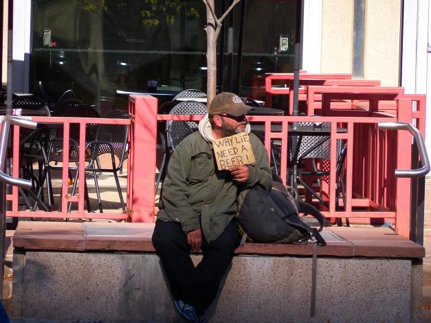 One of the many sign-holding homeless people who beg for money, food, drugs, or in this case, alcohol. These kinds of signs often perpetuate the misconception that all homeless people are lazy alcoholics and drug addicts. Photo taken October 13, 2013.