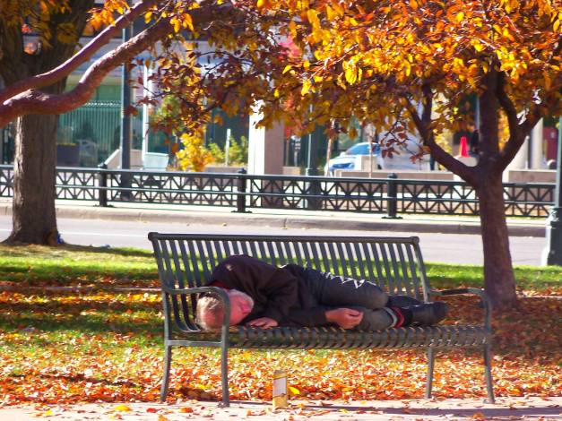 A homeless man asleep on a bench in the park. Police came and roused him and made him leave the park shortly after I took the photo. Photo taken October 27, 2013.