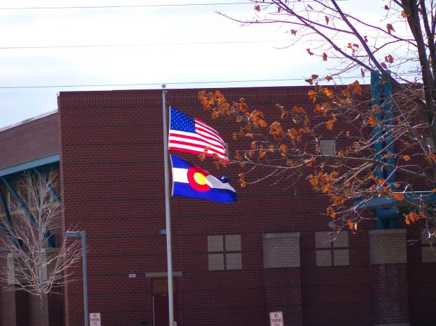 The American flag and the Colorado state flag illuminated by the sun and flapping in the wind. Photo taken November 4, 2013.